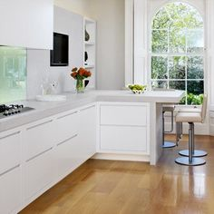 White L-Shaped Kitchen with Glass Splashback, Composite Worktop and Wood Flooring