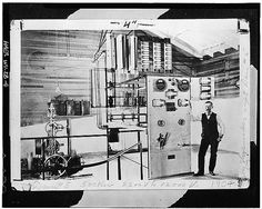 4.  Photocopy of photograph, c. 1904. INTERIOR OF ORIGINAL POWER HOUSE, SHOWING M.P.C. SUPERINTENDENT H. B. SHOEMAKER BESIDE SWITCH. AT LEFT IS A REPLOGLE RELAY WATER WHEEL GOVERNOR THAT CONNECTED TO TWO OF THE THREE TURBINES. (Courtesy of the Potomac Edison Company Library, Historical Data Files, Dam No. 5 listing) - Dam No. 5 Hydroelectric Plant, On Potomac River, Hedgesville, Berkeley County, WV