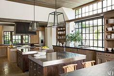 Sconces from Urban Electric Co. illuminate the sink areas, and pendant lights designed by Rela are installed over the stainless-steel islands; Thermador refrigerator and freezer columns (one unseen) bookend the far counter, and the range is by Wolf.