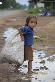 A young girl in Kampong Cham, Cambodia, collecting used plastic bottles to sell for a few pence