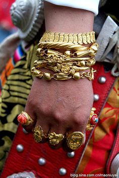 Ngawa, Amdo, Tibet | Jewelry worn by a Amdo Tibetan woman from Ngawa (same woman as previous pin). She wears many heavy strands of coral, and solid 24k gold bracelets on her wrists and 24k gold rings on all ten fingers, some inset with coral. Wearing this ostentatious amount of jewelry is saved for very special occasions such as weddings and annual festivals. Photo by Ge Jialin (葛加林)