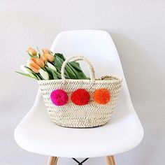 The Mini French Market Basket from Bohemia is an adorable basket handwoven from palm leaf with a natural sisel cord handle with 3 bright and fun pom poms on eac
