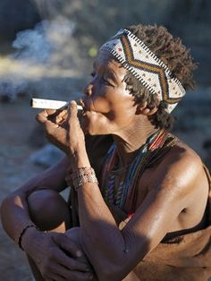 Africa   A woman from the N!!S hunter-gatherer band enjoys a smoke. The N!!S are a part of the San people, often referred to as Bushmen. They differ in appearance from the rest of black Africa having yellowish skin and being lightly boned, lean and muscular. They speak with four distinct click consonants.  Namibia-Botswana border, Botswana   © Nigel Pavitt