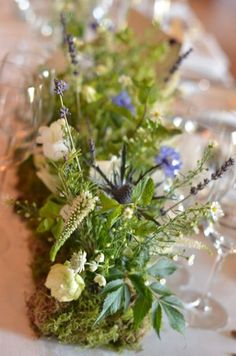 Spriggs Florist, Petworth. Goodwood House Woodland Inspired Wedding. Long tables decorated with mossed blocks, native flowers in mainly white with a touch of blue.