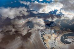 The blue sky and clouds are reflected in the oily waste water of a tailings pond for the Alberta tar sands