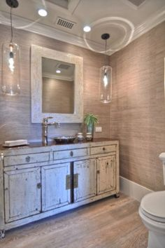 This bathroom is a textural feast. With its sand-colored grass cloth, distressed white paint and oversize glass pendants, it has all the textures of the beach.