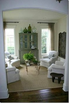I love the airy and light feel in this room.  Sisal rug, small table, 4 matching chairs, light drapes.