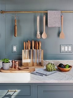 French blue cabinets and wall color pairs perfectly with marble, brass and copper kitchen accents.