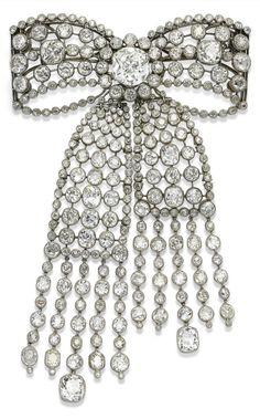 A BELLE EPOQUE DIAMOND BROOCH, 1910S. Designed as an openwork bow, suspending an asymmetrical articulated ribbon pendant, set throughout with old-cut diamonds, to the collet-set old-cut diamond fringe terminals, 12.5 cm. #BelleÉpoque #brooch