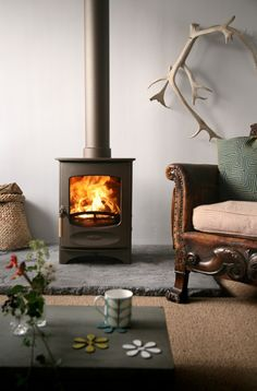 A wood burning stove has a flat bottom on which the wood burns on a bed of wood ash. Wood burns more slowly in a woodburning stove. Hearth Pad, Wood Stove Hearth, Granite Hearth, Slate Hearth, Corner Wood Stove, Fireplace Stores, Stove Fireplace, Fireplace Design, Cottage Fireplace