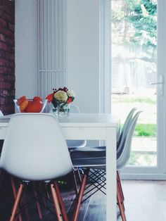 Flowers, white dining table, Eames white chairs, exposed brick wall, patio door.