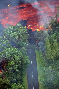 """""""Aerial view taken 02 April 2007 of lava coming from the Piton de la Fournaise volcano burning vegetation and road in the Indian Ocean island of La Reunion. Time In The World, Wonders Of The World, Dame Nature, Big Island Hawaii, Natural Phenomena, Hawaiian Islands, Aerial View, Amazing Nature, Mother Earth"""