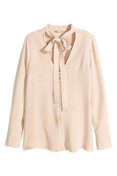 Blusa de seda: QUALIDADE PREMIUM. Blusa de seda natural com laçada no decote em V. Tem botões forrados na frente e nos punhos e racha alta nos lados.                                                                                                                                                                                 Mais