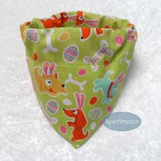 Easter Puppies Dog Bandana: Colorful canines wearing bunny ears, decorated Easter eggs and doggie bones are the featured designs of this whimsical Spring bandana. The glittery fabric has pink Pugs, robin's egg blue and golden Terriers and orange Doxies, all wearing pink bunny ears that will have you laughing out loud!  Order as either a Scrunchie Bandana with an elastic neck or as a Collar Slipcover-style bandana. | SewAmazin @sewamazin  #indiemade #ButterflysPin