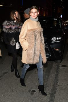 Olivia Palermo wears a fur coat, grey turtleneck knit and skinny jeans