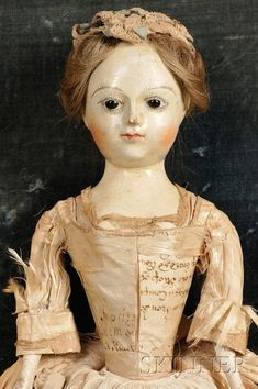 Queen Anne Memorial Doll c.1735, carved wooden head & torso, jointed wooden legs. Leather arms with wood hands, glass eyes, painted brows & lashes, blushed cheeks & human hair wig. Silk dress with paper bodice. Likely French.