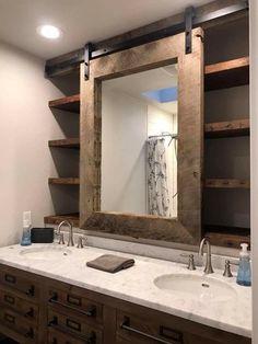 Bathroom with barn door rolling mirror. Shelving behind.