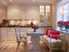 Cozy christmas kitchen.  I love the comfy couch/bench and the white star in the window.  Beautiful simplicity.
