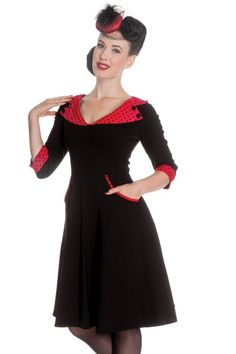 Rona vintage style dress by Hell Bunny is made from stretchy black bengaline fabric witha collar made from red polkadot fabric and detailed with2black fabric covered buttons on either shoulder.