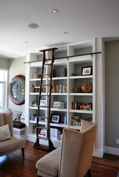 I don't want a rolling ladder (it's a space hog), but I like the gray and white walls, the dark wood floors, and the simple wing chairs.