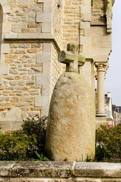 Stèle de Reguiny.Bretagne:Morbihan (56).By the church in Reguiny there is a stèle which has been Christianised by the addition of a cross to the top.The stèle is conical & rounded and just over a metre tall. The stèle was moved to this site from another location when consolidation took place.It can be seen from the road & there is a free car park at the rear of the church & a flat paved area so disabled people can view the stone.