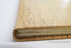 Nina Judin's book is bound in craquelle leather and closed with straps.