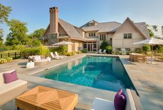 Oversized deck with multiple lounge areas and a full-length bench in the pool #pool #luxury #backyard
