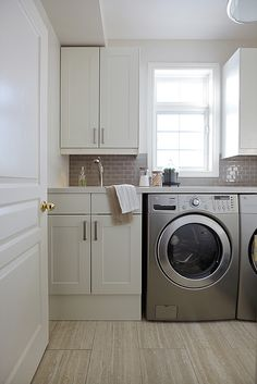 White and gray laundry room boasts creamy white cabinets paired with off-white countertops and gray mini subway tile backsplash. A small laundry room sink sits next to silver front-load washer and dryer placed under window. Laundry Room Colors, Grey Laundry Rooms, Laundry Room Remodel, Laundry Room Cabinets, Laundry Room Organization, Laundry In Bathroom, Mud Rooms, Small Laundry, Laundry Closet