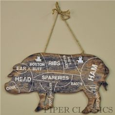 """This charming Pig Plaque with vintage appeal has a traditional farmland silhouette of a pig, but showing the cuts for a butcher shop. Perfect for a country or farmhouse kitchen with rustic or primitive decor. Two clips are attached for hanging notes or photos; twisted rope cord for hanging on wall. 22"""" long x 12.5"""" high."""