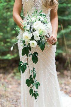 On aime aussi ce bouquet, plus minimaliste, dont une seule longue tige garnie de feuilles tombe en cascade. Sans elle, le bouquet aurait une forme plus classique. Cette composition est faite de roses blanches, de dahlias, d'eustomas et de lierre. Romantique, non ?