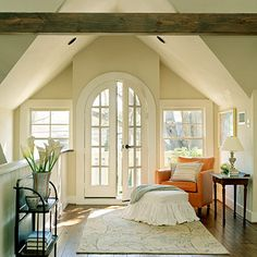 French doors and double hung windows bring sunlight flooding into the cozy reading corner of this master bedroom.