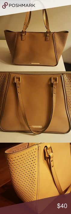 Vince Camuto Tan Leather Tote! 100% genuine soft leather. Perforated side panels. Partially lined. Snaps closed. Used condition, but looks good! Some faint marks on the solid panels & 2 deeper scrapes on the bottom.  Millimeter size crack in leather were 2 panels meet. Pen marks on inside.  Note- I am not the original owner of this beautiful bag. I bought this at designer consignment store, but never used myself. It does NOT have tassel or duster. I would like to find it a new home where it…