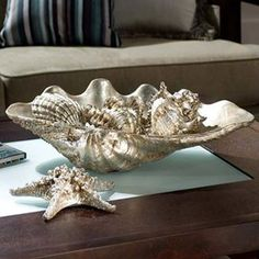 This antique silver shell set imparts an upscale coastal look as a coffee or dining table centerpiece. An elegant accent piece, a large shell cradles smaller seashells finished in an aged metallic. #homedecor #beachdecor #IslandLife #interiordesign #coast
