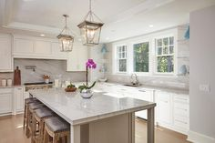 Fantastic white kitchen features floating lucite shelves and quartzite countertops with pops of blue.