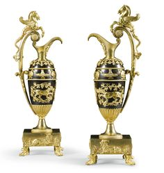 A pair of Russian gilt-bronze and bronze ewers 19th century, in the manner of Friedrich Bergenfeldt, of tapering baluster form, the scrolled handle cast with a hippocamp, the spout with a bearded male mask, the body with two swans flanking a fountain, the lower section with two lionesses enclosed by vine leaves and grapes, the rectangular base cast with a recumbent ram, on paw feet  each 47cm. high; 1ft. 6½in.