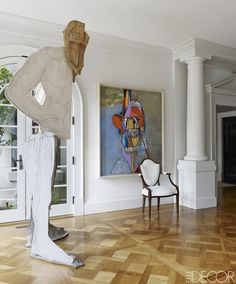A painting by George Condo, an Adam-style armchair, and a sculpture by Thomas Houseago in the main hall.   - ELLEDecor.com