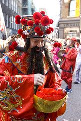 God of Wealth passing out Lucky Red Envelopes (huang bao or ang pow) from a gold ingot bowl