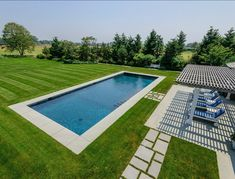 Simple and beautiful. Perfect place to spend your summer. Natural stones are the focus in most Hamptons estate backyards. Oh! And green green grass!