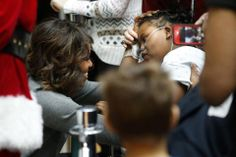 """First Lady Michelle Obama talks with a young patient during a visit to the Children's National Medical Center in Washington, December 16, 2013. The First Lady read the book """"'Twas the Night Before Christmas"""" before greeting the children along with Santa Claus and presidential dogs Sunny and Bo."""
