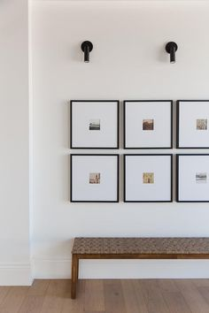 Stacked picture gallery frames are lit by matte black picture lights and mounted over a wood and fabric bench. Interior Styling, Interior Design, Home Goods Store, Moise, Interior Exterior, Entryway Decor, Entrance Foyer, Home Decor Inspiration, Decoration