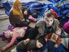 Síria acomoda seus filhos depois de serem resgatados de um barco de pesca que levava 219 pessoas que tentavam entrar na Europa (Foto: UNHCR / A. D'Amato)