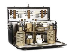 A vintage picnic set circa 1901.  It consists of a black leather case with nickel plated handles which open to reveal a decorative wicker framework interior fitted with leather covered flasks, wicker cased drinking bottles, and gilt edged bone china cups and saucers.