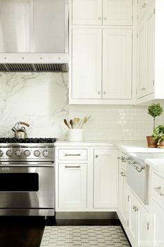 white traditional kitchen white tile backsplash calcatta countertop walnut top island farm sink