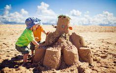 Kinder am Sandburg bauen