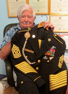 David Eshelman holds his command sergeant major's dress uniform he wore while serving as the top enlisted man in the Army. He plans to be buried in the dress uniform. (Sun photo by Don Moore)