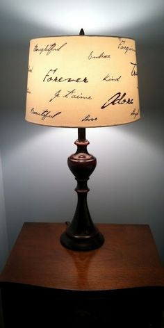 First, print out the words in your favorite font and trim around them.  Then, tape them to the inside of your lamp shade with the light on.  Use a permanent marker to trace the words on the outside of the shade.
