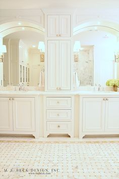 arched mirrors, double sinks, white footed cabinets
