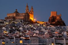 The quintessential Spanish town of Olvera, Cadiz Province, Andalucia, Spain photographed at dusk. The skyline is dominated by the church of Parroquia de Nuestra Señora de la Encarnación and the adjacent Arabic castle.