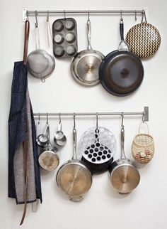 I like my pot/pan rack from IKEA, but this is a smart idea, you could use a cute curtain rod, and than the hooks from IKEA or elsewhere. you could also use it as a coat rack.