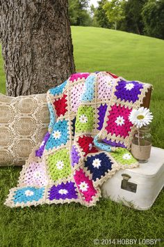 Waffle-style pattern. Groovy color scheme. Comfy & cozy! What's not to love about this daisy-dotted afghan?